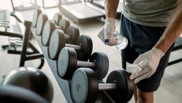 Unrecognizable,Athlete,Spraying,Dumbbells,With,Disinfectant,In,A,Health,Club.
